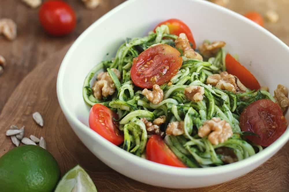 A bowl of Zucchini pasta on a wooden chopping board.