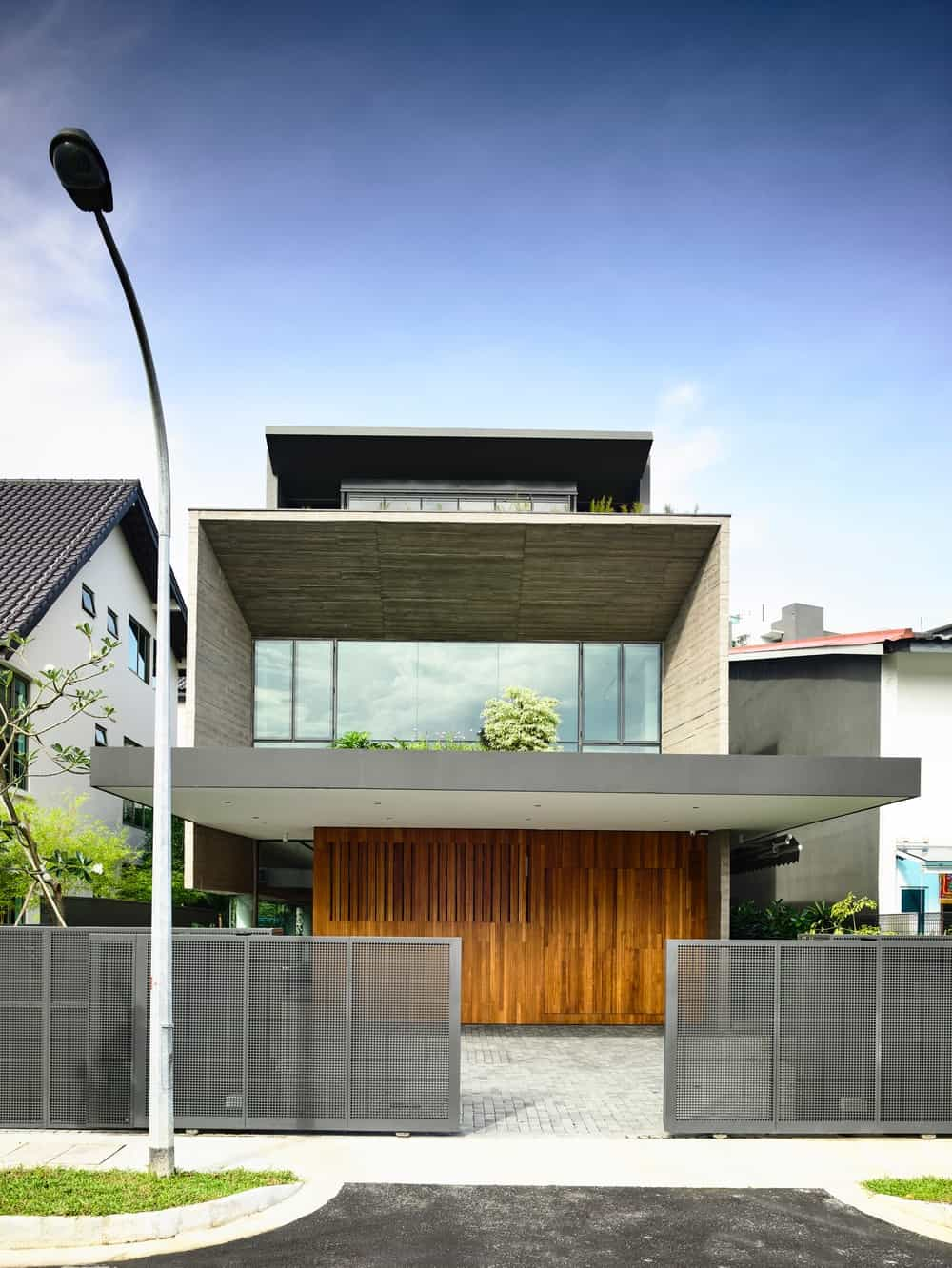 The driveway leads to the wood-toned garage doors of the house topped iwth a large glass wall on the second level.