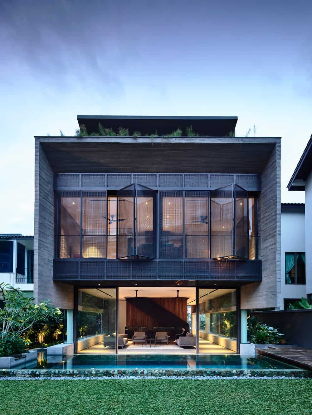 This view of the back of the house showcases a glass-walled ground floor with a pool on the side and an opaque-paneled second level with a warm glow.