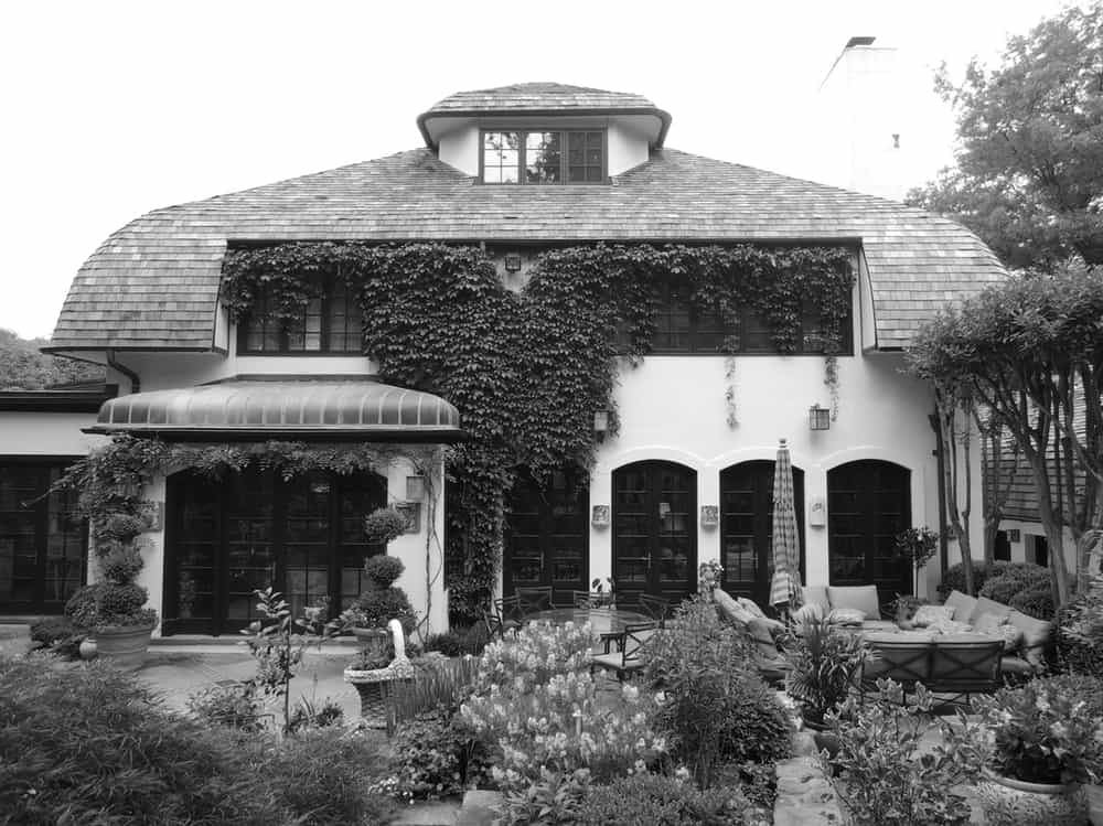 This is a black and white view of the front of the house before renovation adorned with creeping vines on its exterior walls that set a background for the sitting area.