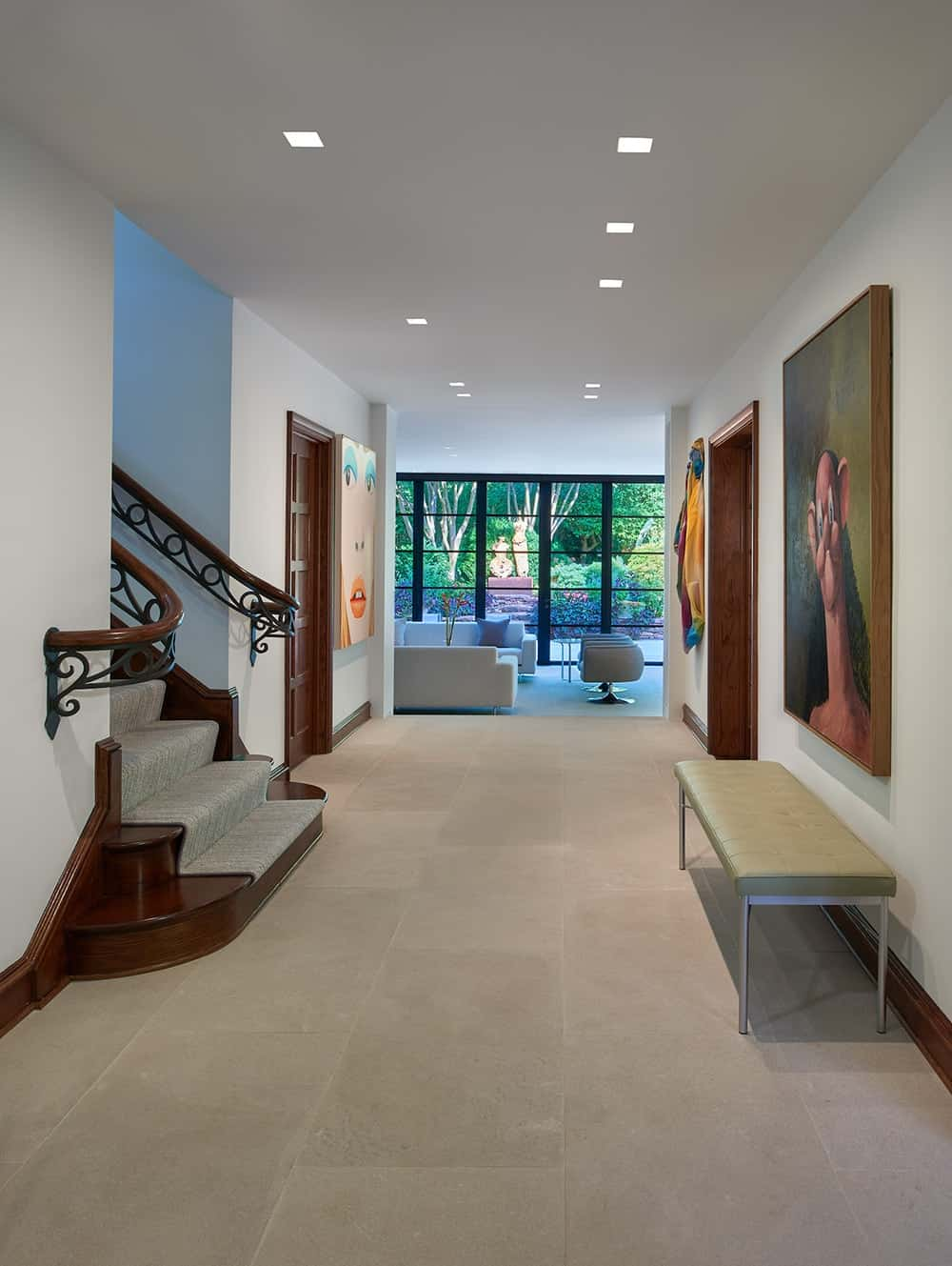 Upon entry of the house, you are welcomed by this foyer that has a cushioned bench under a large painting across from the foot of the stairs.