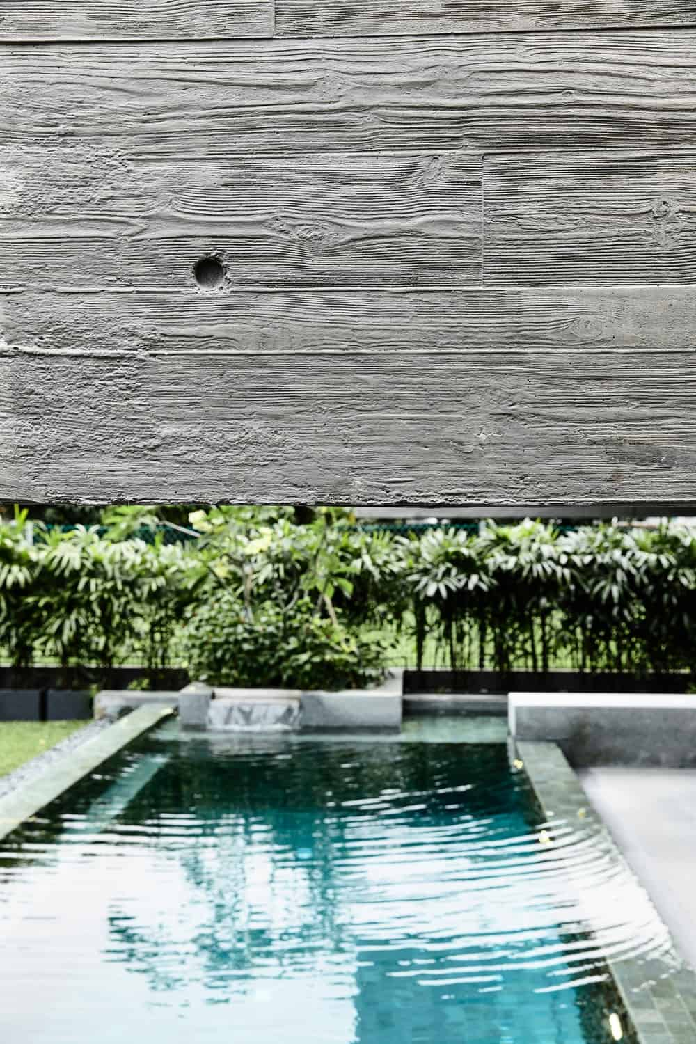 This is acloser look at one of the exterior walls revealing its textured gray surface with the pool area in the background.