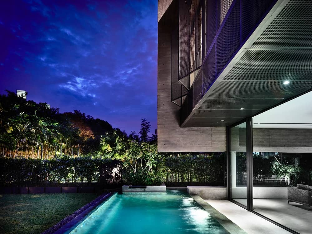 This nighttime view of the pool shows its own lighting that give it an ethereal glow paired with the exterior lighting of the shrubs.