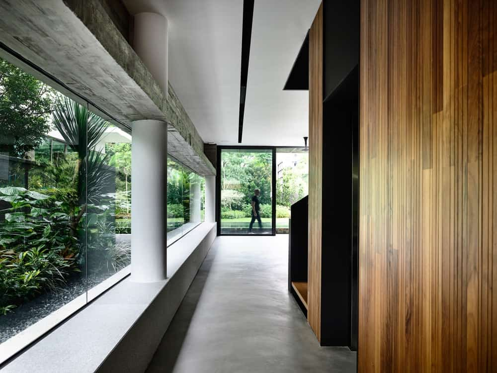 This is a hallway that leads to the staircase with glass walls on one side bringing in an abundance of natural lighting.