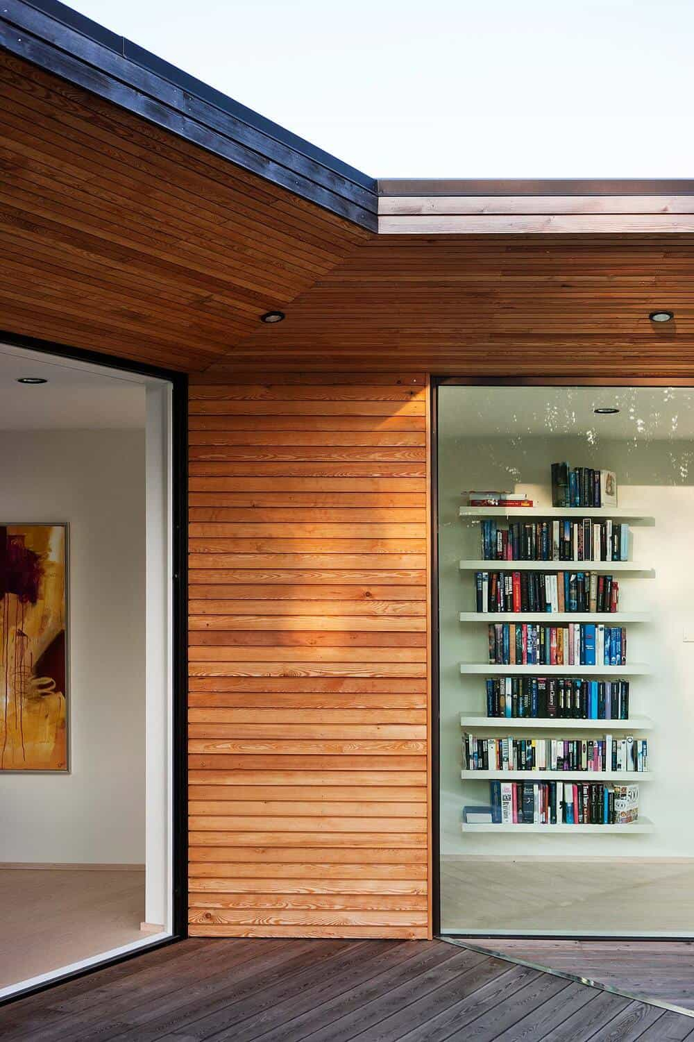 This is a view of the interior wall from outside the glass wall.Here you can see that there are built-in floating bookshelves.