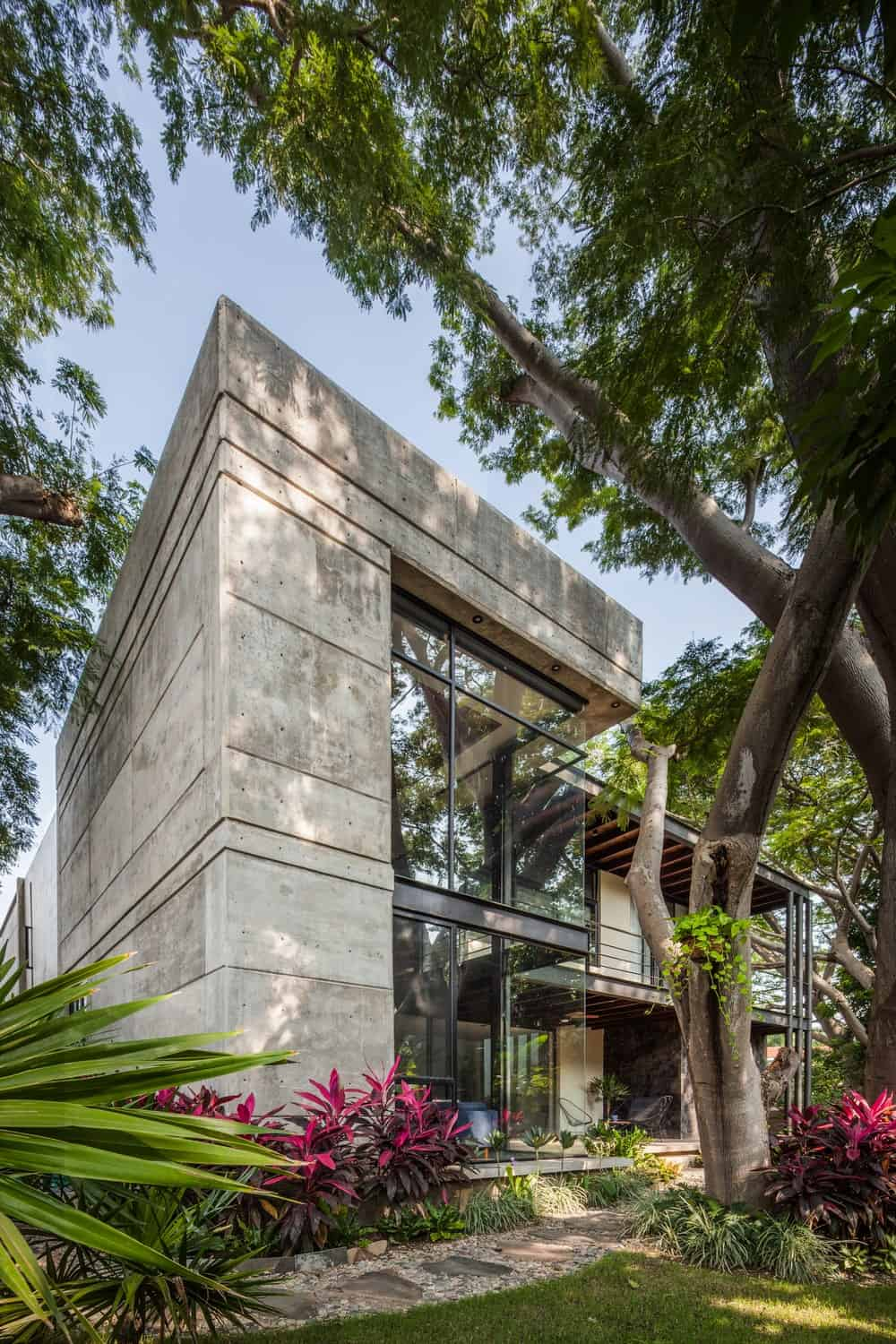 This is the back of the house featuring a large concrete structure that supports the glass walls on two levels at this side of the house.