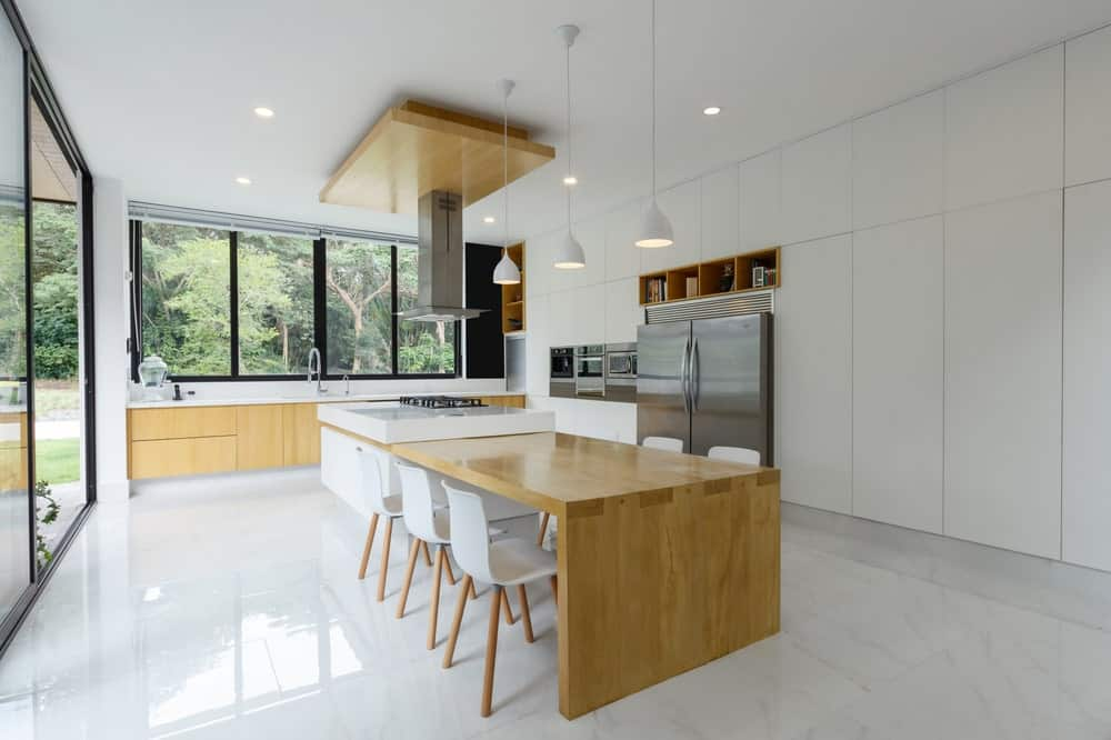 This is a closer look at the kitchen with bright white floor, walls and ceiling that makes the wooden elements and stainless steel appliances stand out.