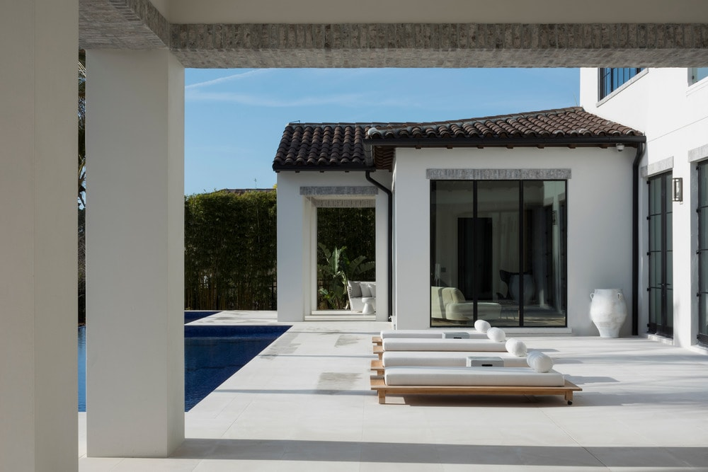 This is the poolside area with a row of lounge chairs across from the pool on concrete walkways that match the exterior walls of the house that is adorned with large glass walls.