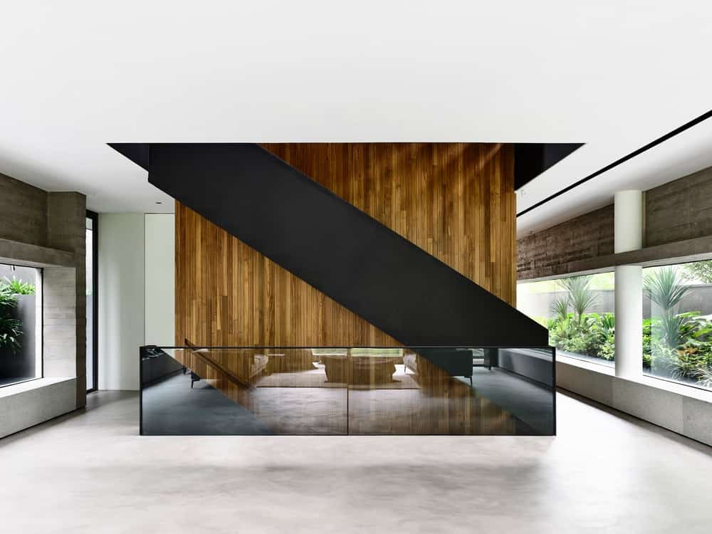 This is a look at the second-floor landing with a balck staircase paired with opaque glass railings for a unique combination with the wood-paneled wall and glass walls.