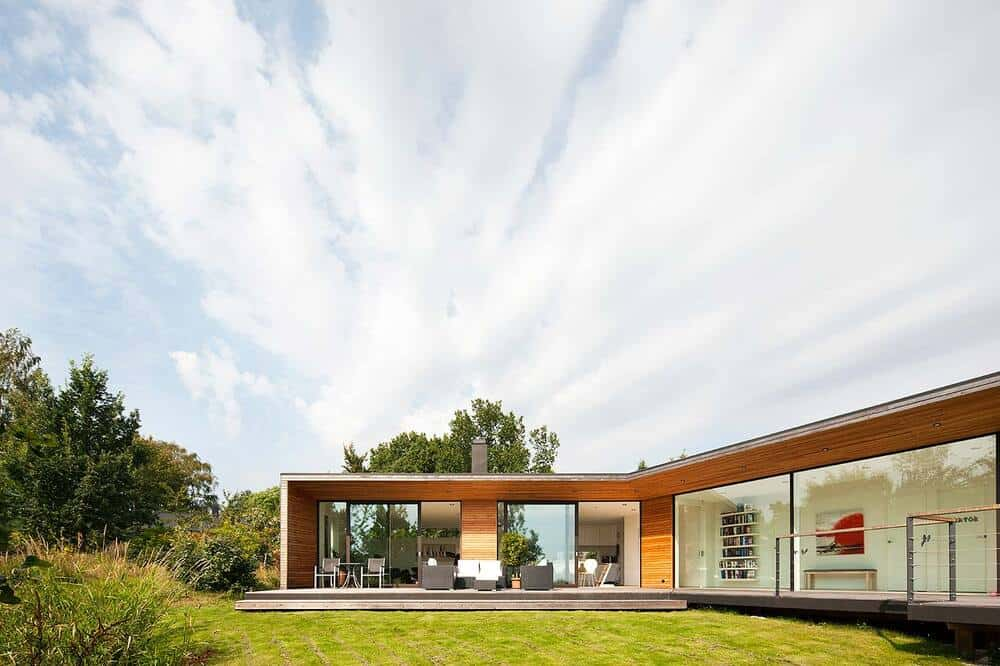 This exterior view of the house showcases more of the glass walls that open to the elevated wooden deck patio.