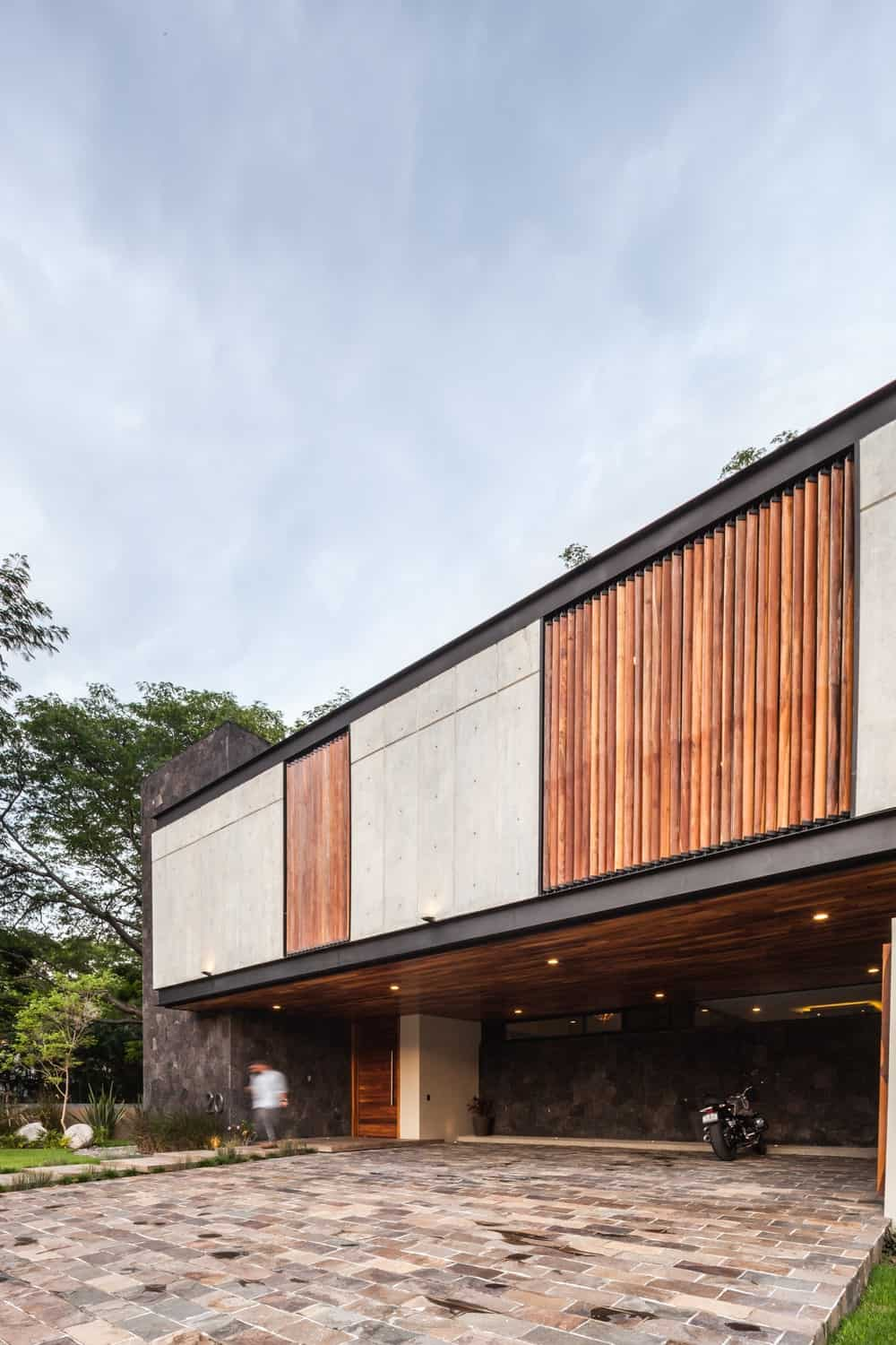 This closer look at the front of the house showcases the concrete walls of the second kevel adorned with bamboo walls that matches with the ceiling of the car port underneath.