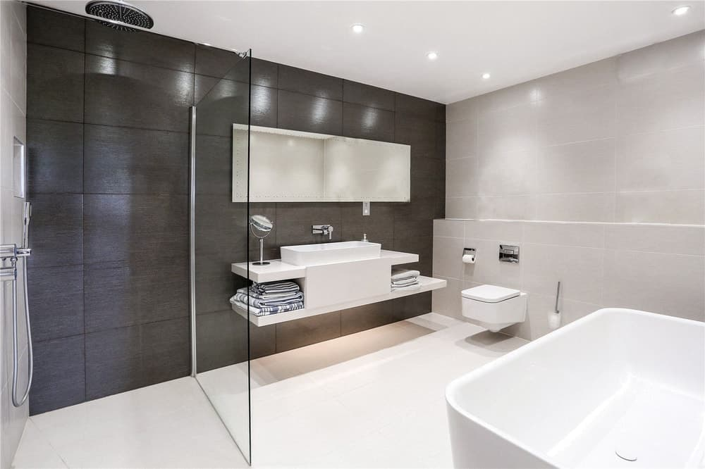 The bathroom has modern floating white vanity and toilet with a half-wall of glass.