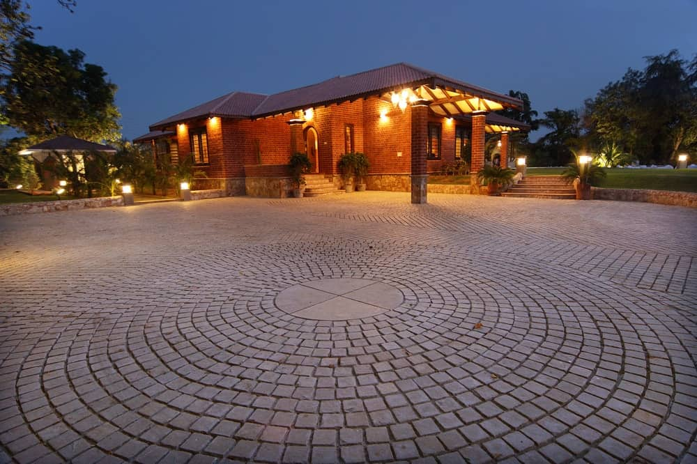 This is a look at the house with brick exteriors that match the brick walkway and driveway leading up to the house that is illuminated in warm exterior lighting.