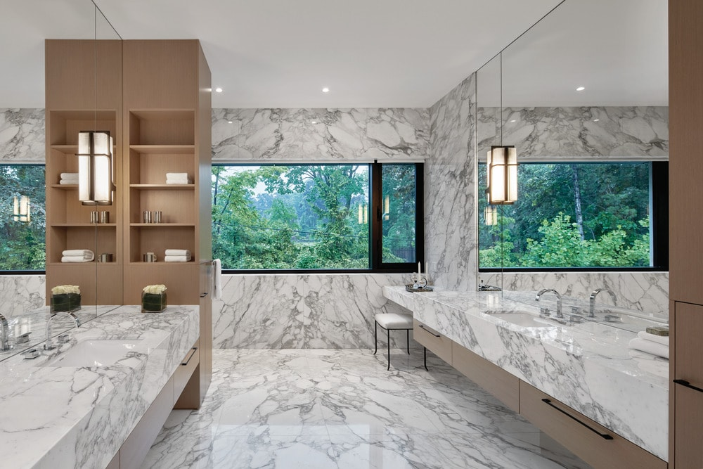 This bathroom has a consistent white marble tone on its floating vanities and walls that make the mirrors and cabinetry stand out. These are then illuminated by the large wall on the far side.