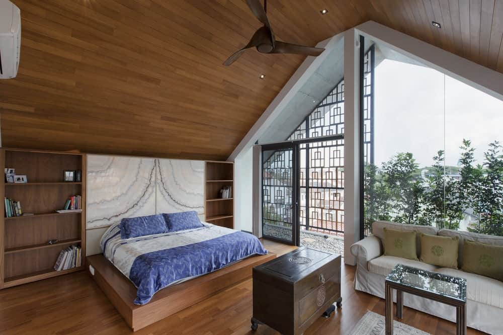 The primary bedroom has a large wooden platform bed that matches well with the tall wooden cathedral ceiling.