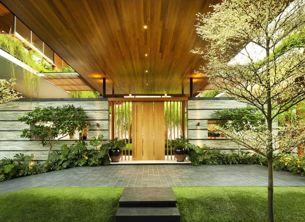 This is the view of the outer entrance to the courtyard. the wooden door matches well with the ceiling above with recessed lights. These are then complemented by lush landscaping of shrubs.