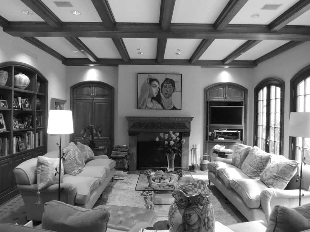 This is a black and white view of the living room of the house before renovation with a more traditional look topped with a beamed ceiling.