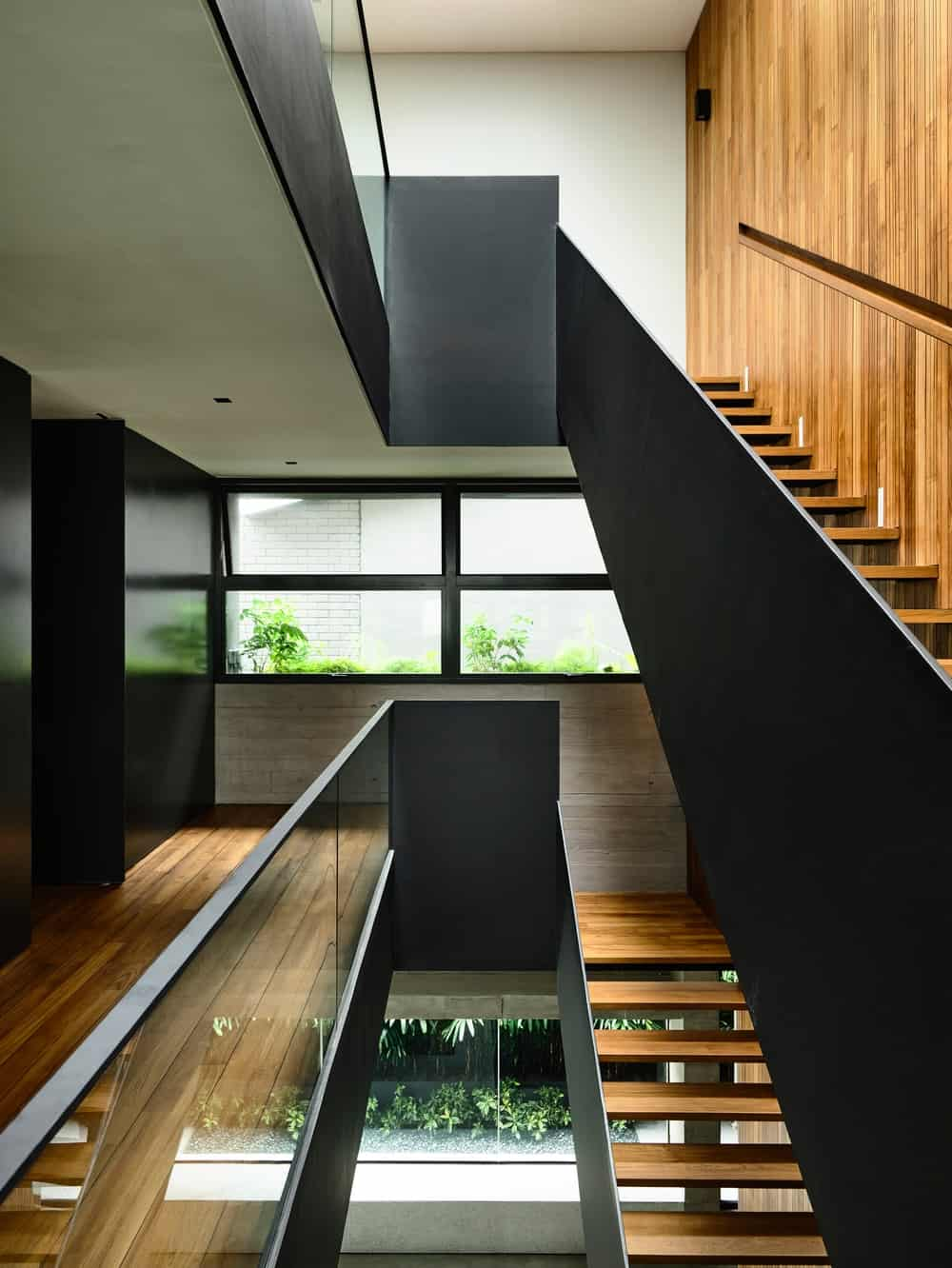 This view of the staircase shows more of the opaque glass railing, black hand rails and wooden steps.