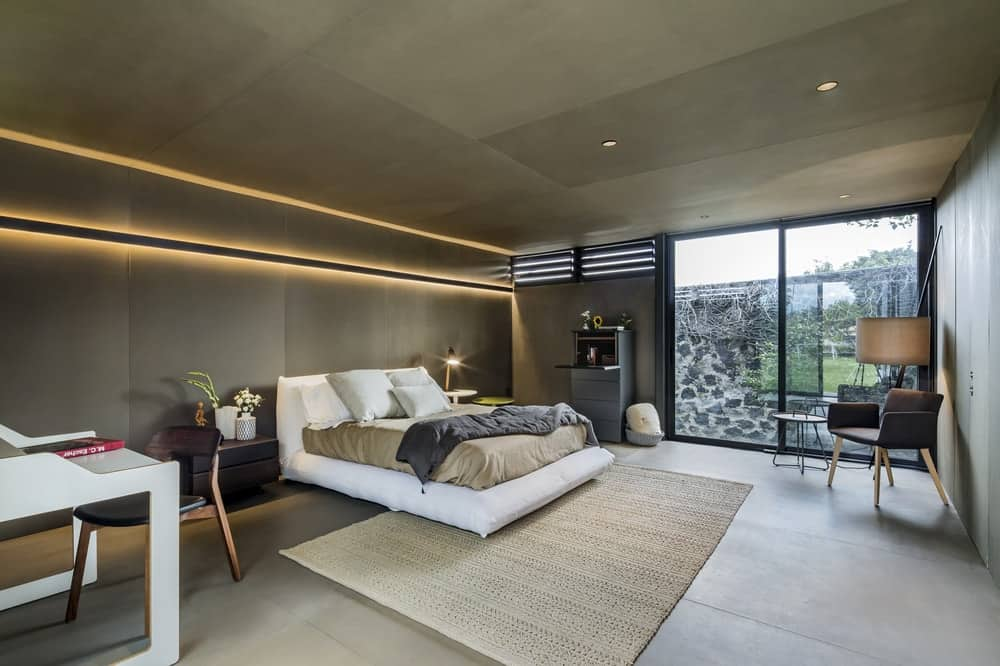 This view of the bedroom showcases the bright white furniture that stands out agaisnt the concrete walls and ceiling adorned with lighting.