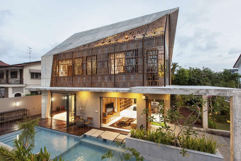 This aerial view of the house showcases the warm glow that escapes from the interiors of the house through the open walls and see-through panels of the second level.