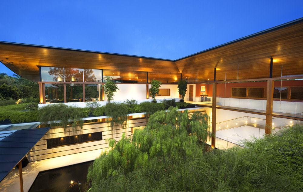 This nighttime view of the house showcases the warm glow of the interior and exterior lights that seem to mesh together complemented by the landscaping.