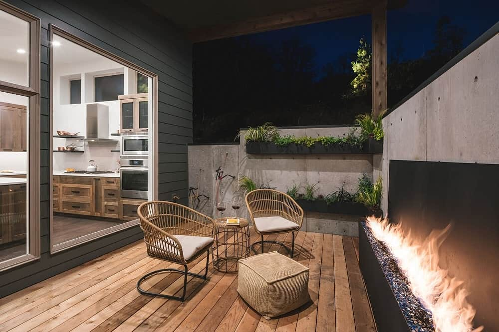 This is a full view of the covered patio that has a set of two outdoor cushioned chairs facing a modern fireplace that pairs well with the wooden deck flooring.
