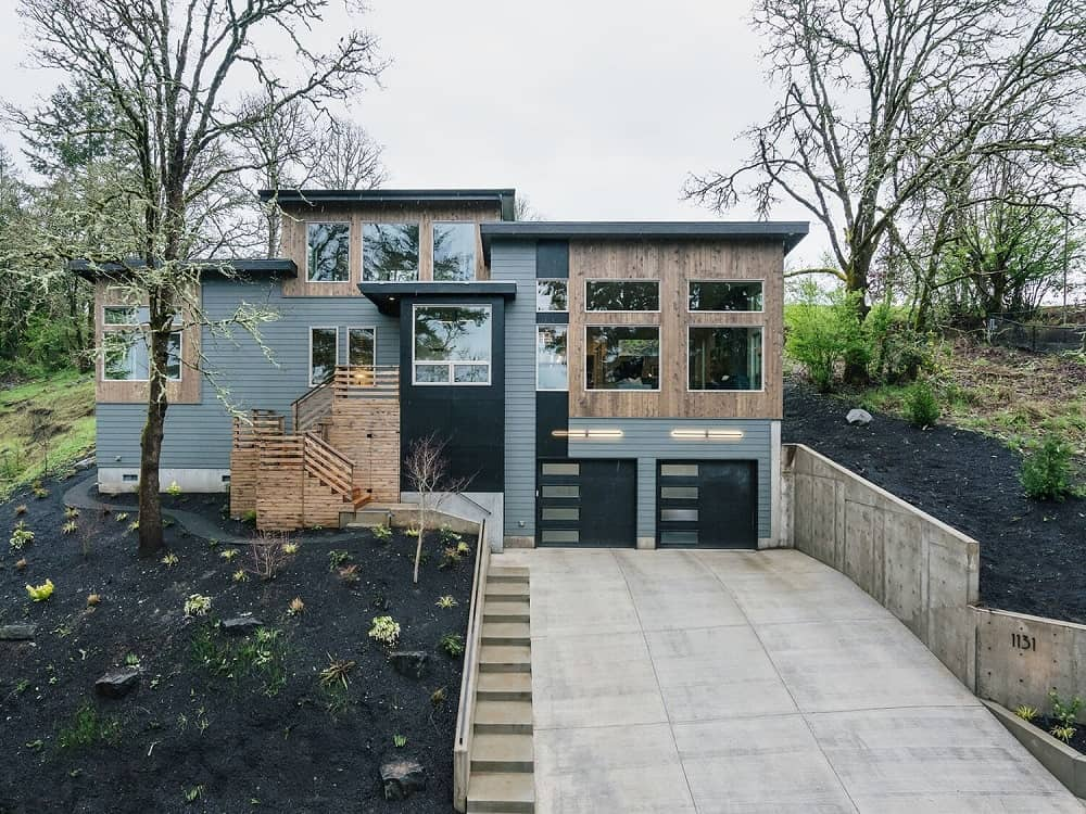 This is a look at the house with well paired tones of wood, gray, black and glass on its exterior walls paired with a wide driveway and a large front yard.