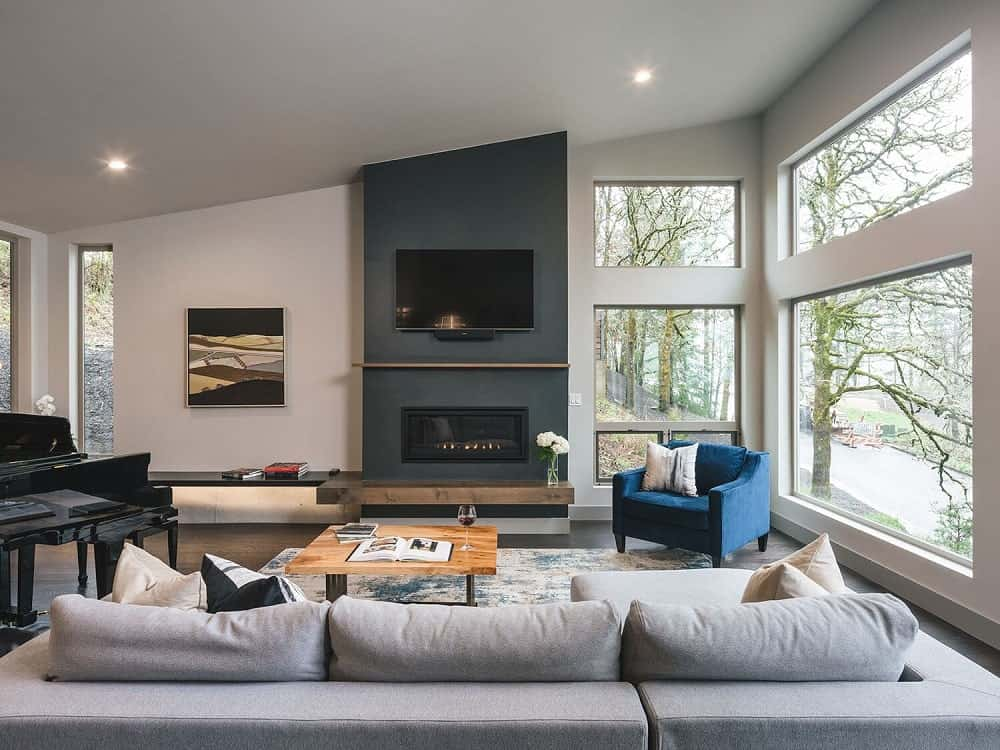 This is the living room that has a large light gray sectional sofa, a wooden coffee table, a blue armchair and large glass walls on the side.