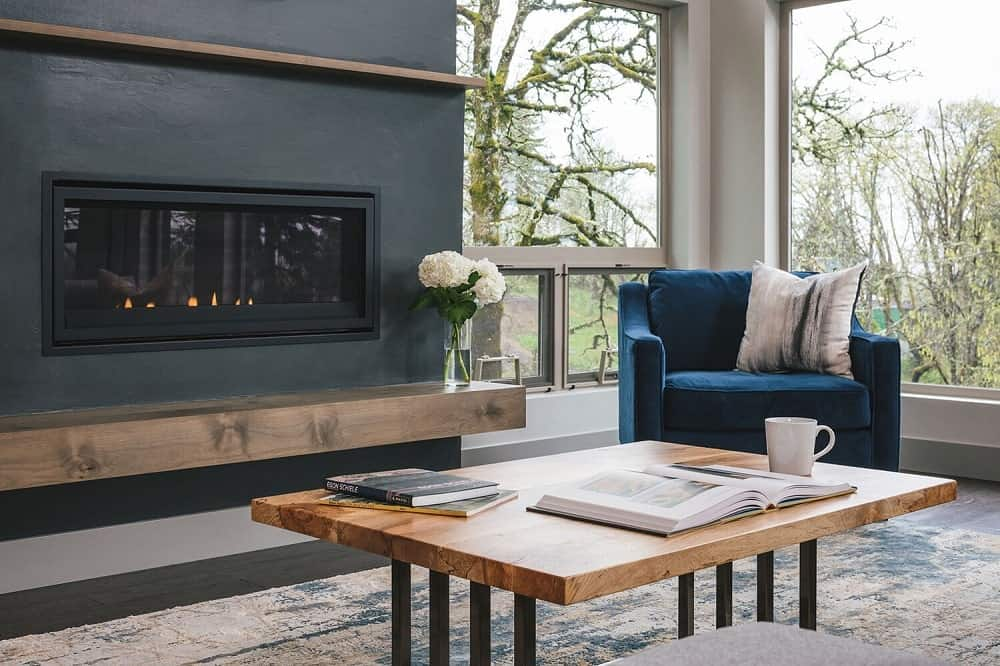 This is a closer look at the wooden coffee table and blue cushioned armchair warmed by the modern fireplace.