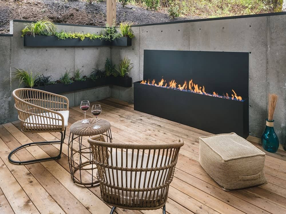This is a close look at the patio with outdoor furniture facing a modern outdoor fireplace.