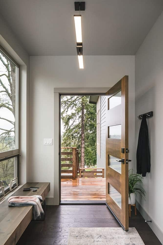 Upon entry of the house, you are welcomed by this small and simple foyer with a wooden door that has opaque glass panels. These are then complemented by the large glass window on the side that brings in natural lighting.