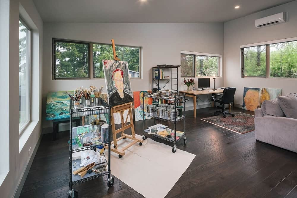This is a look at a painting studio with a home office setup at the far corner.