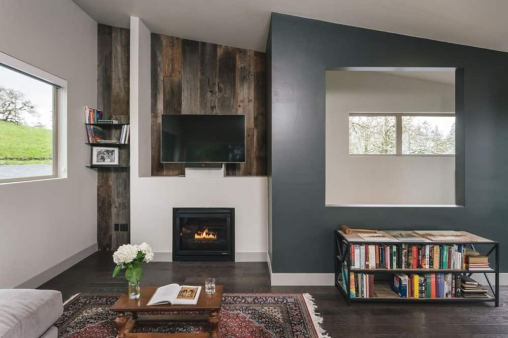 This is a family room with a gray sofa, a small bookshelf, a fireplace and TV supported by the large white structure on the far end.