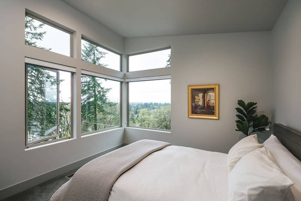 The bedroom has a comfortable bed that is adorned by the row of tall windows that bring natural light as well showcase the landscape outside.