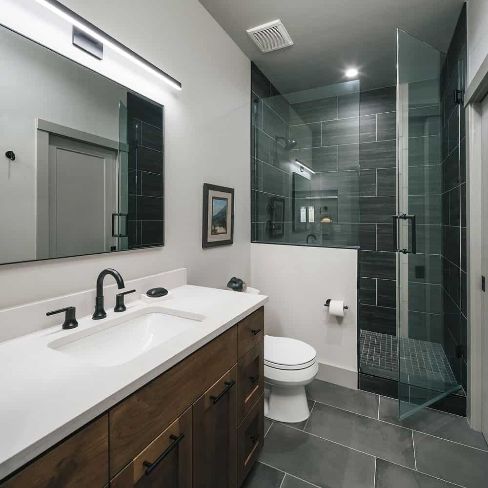 This bathroom has a large wooden vanity with white countertops, a toilet and a glass-enclosed shower area at the far side.