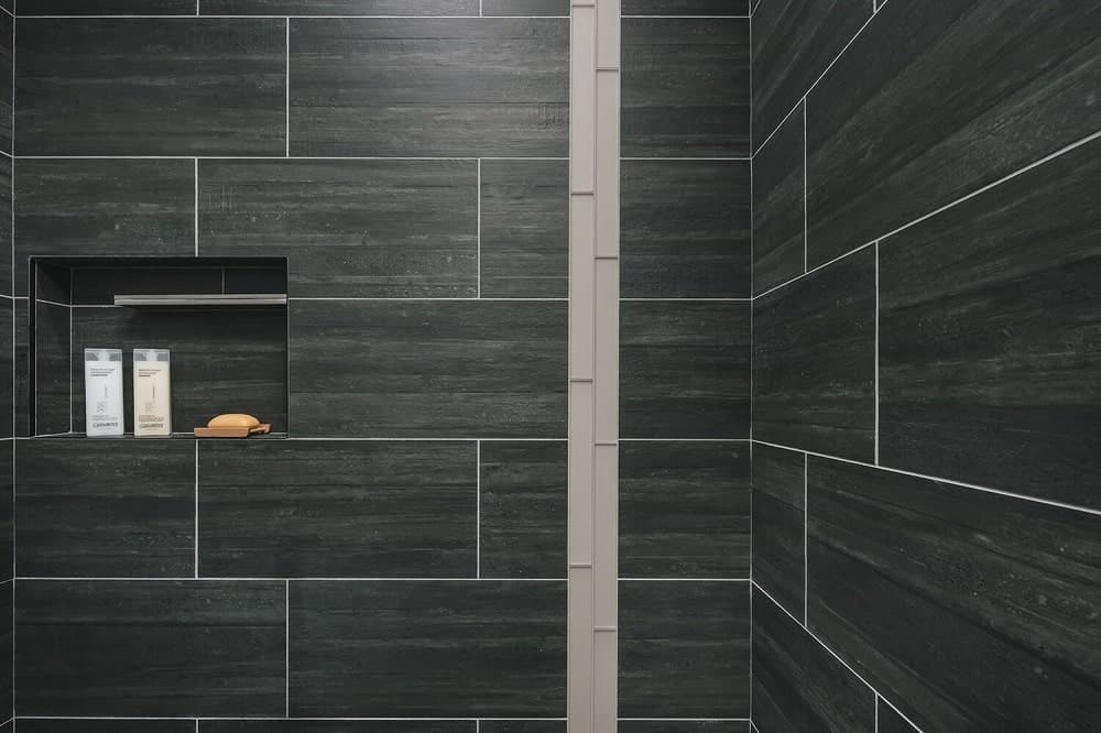 This is a close look at the dark gray tiles of the shower area with a small alcove for the bath products.