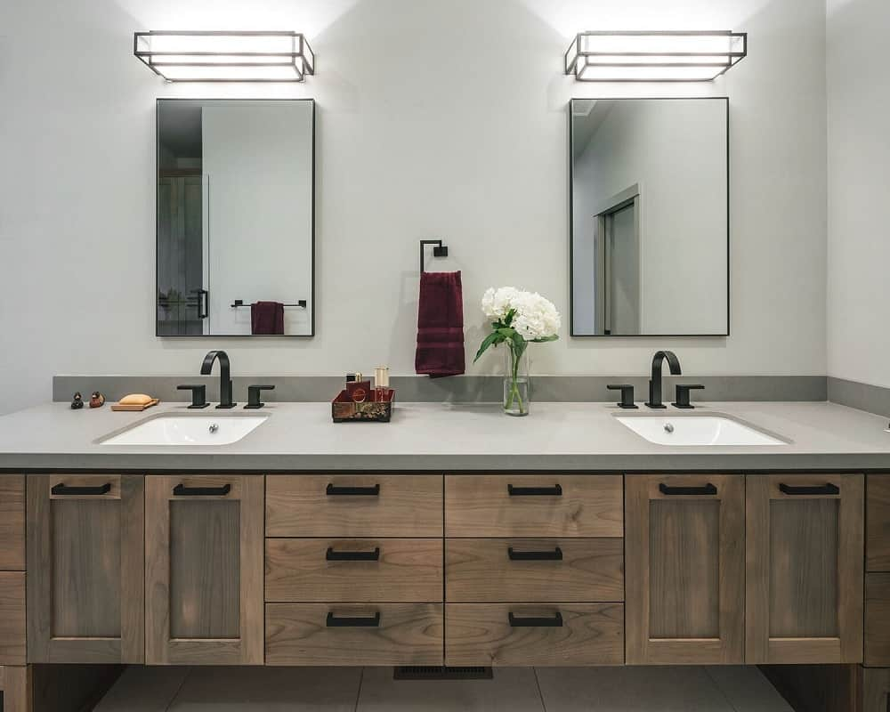 This is a closer look at the two-sink wooden vanity topped with mirrors that are lit by wall lamps above.