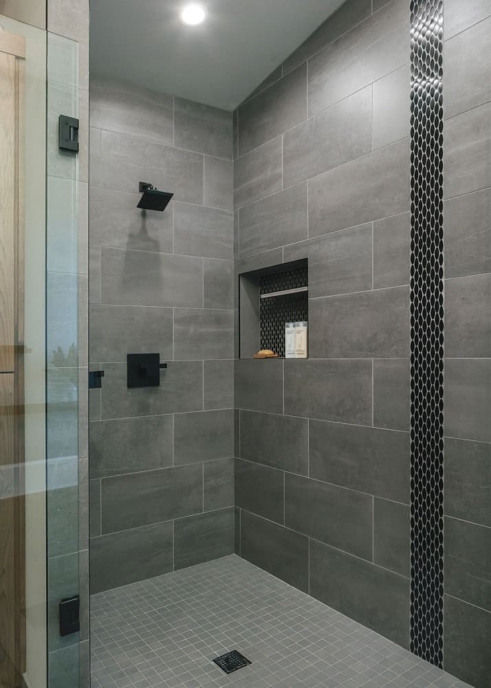 This is a closer look at the glass-enclosed shower area with gray tiles, black fixtures an alcove for products.