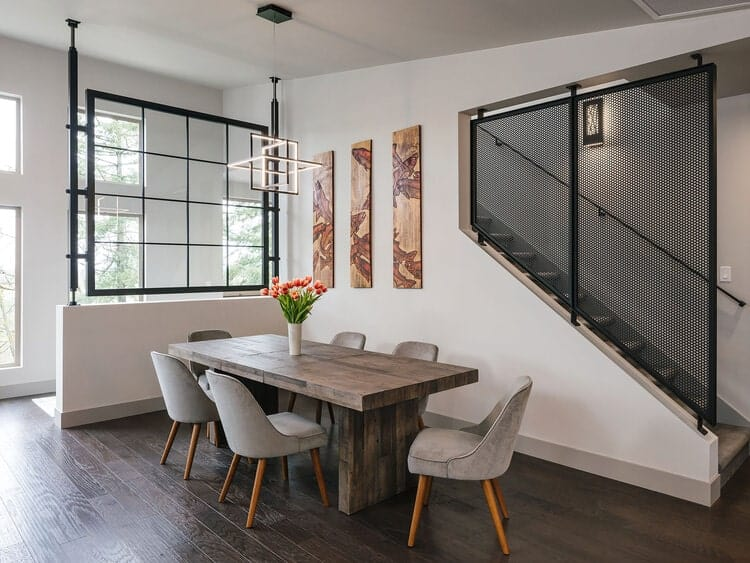 This is a closer look at the dining area that has a long rectangular wooden dining table surrounded by gray cushioned chairs.