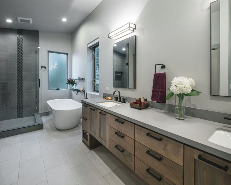 This other bathroom has a large two-sink vanity and a freestanding bathtub at the corner by the windows and the shower area.