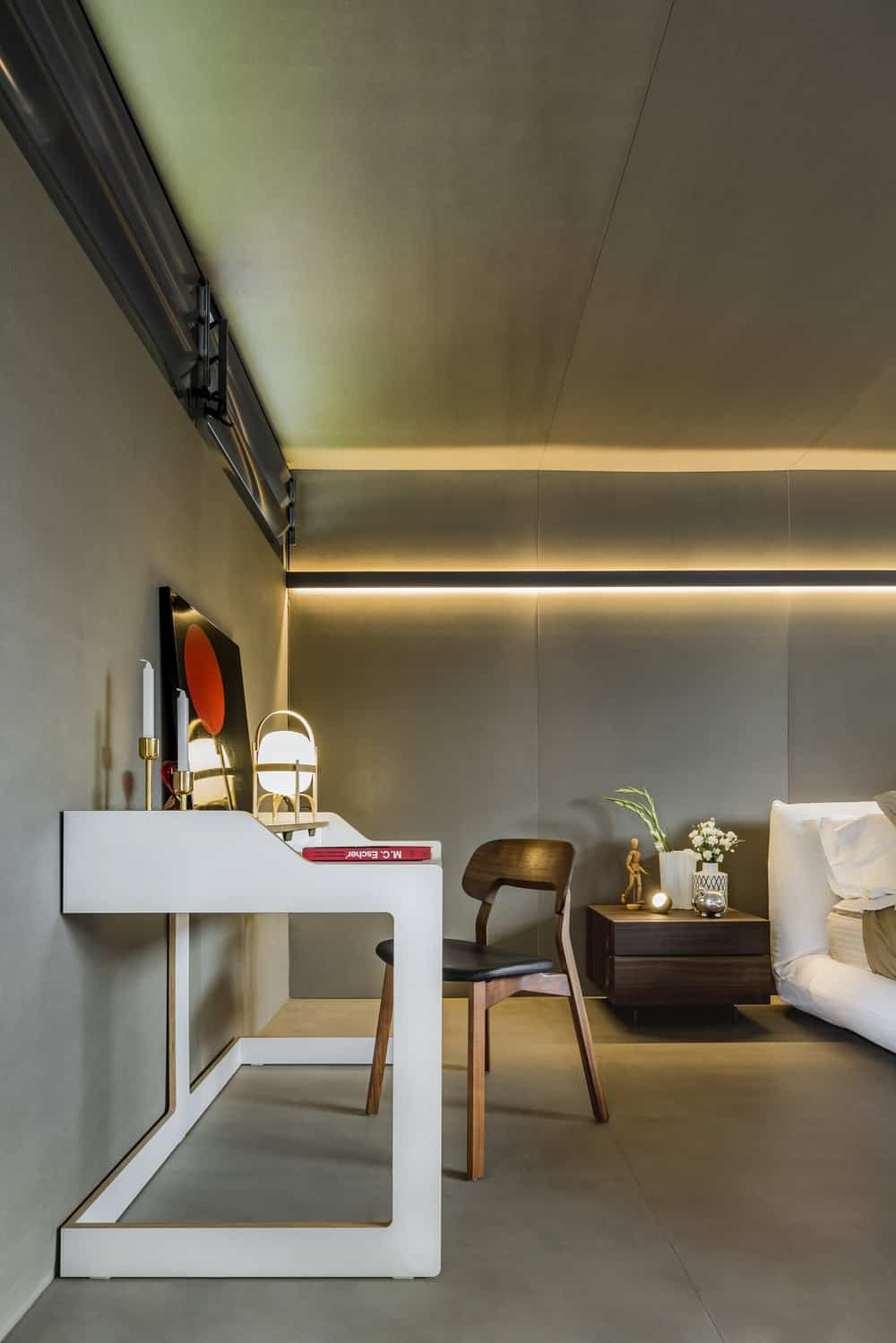 This is a close look at the vanity and study area with a white vanity and study table paired with a wooden chair.
