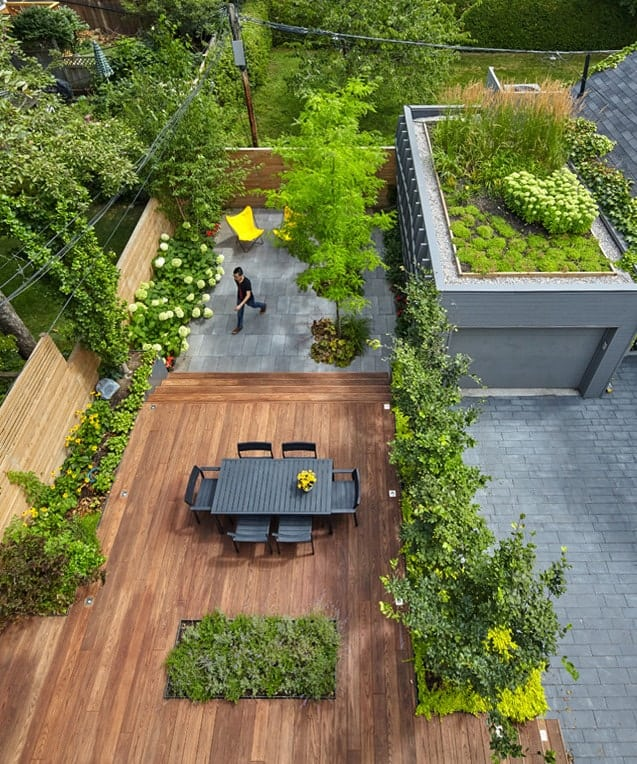 This is a look at the back of the house from the vantage of the balcony. You can see here the wooden deck floor of the patio fitted with a dark outdoor dining set surrounded by landscape of plants and flowers.