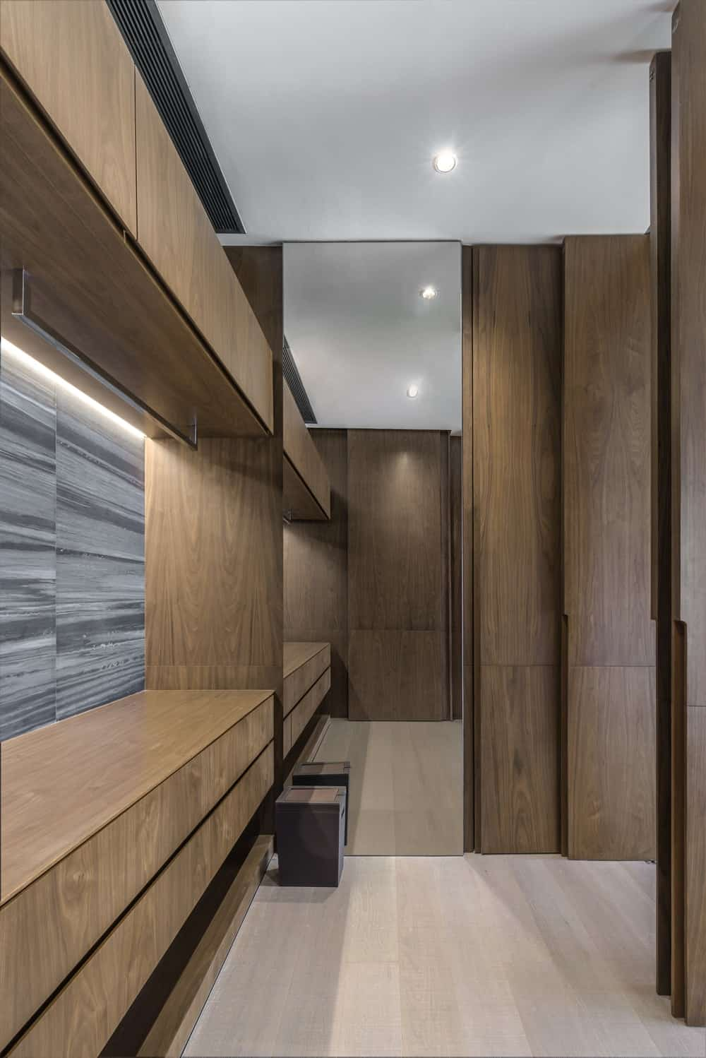 This is the bathroom that is dominated by wooden structures with cabinets and drawers.