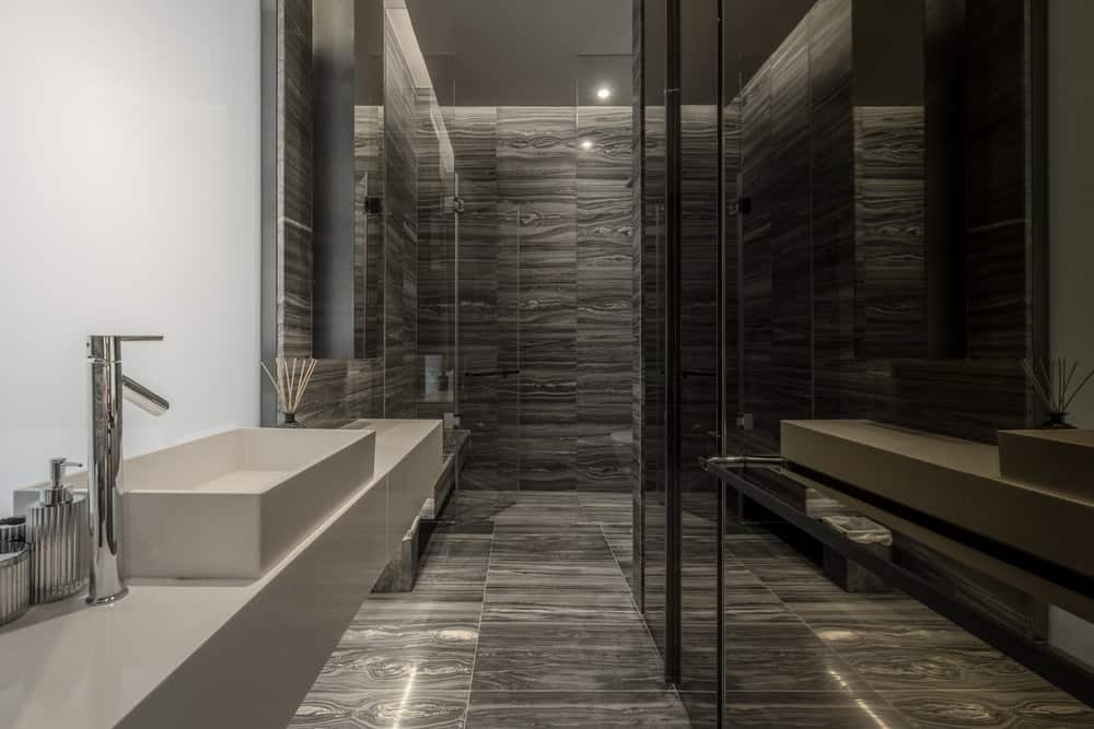 Across from the modern floating vanity of the bathroom is a set of dark glass doors that serve as entrance to the bathroom.