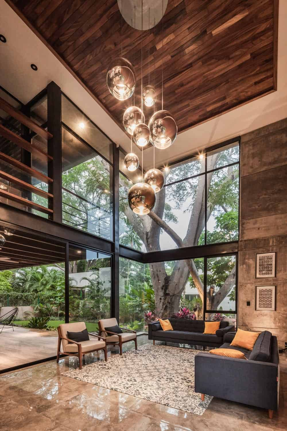 This is the warm glow of the living room that is complemented by the lush landscape just outside the glass walls.