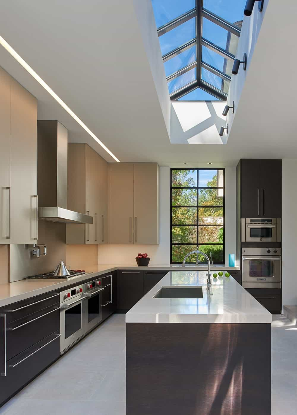 The kitchen is illuminated by the large cathedral skylight above the kitchen island that brings in an abundance of natural lighting.
