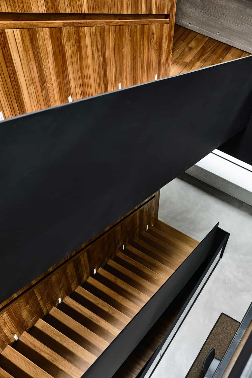 A look adown the third level of the house down into the two sets of staircase with black walls and wooden steps.