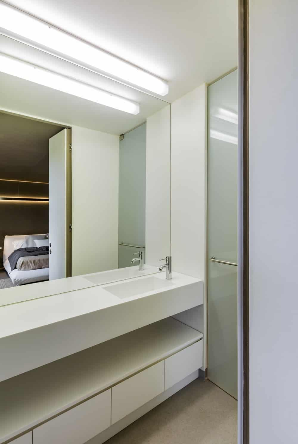 This is a close look at two-sink floating bright vanity of the bathroom topped with a mirror and a lamp.