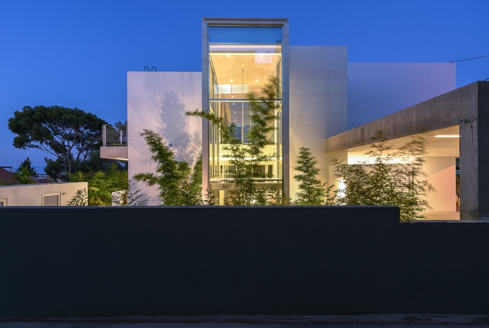 This is a closer look at the dark outer wall that is contrasted by the brightness of the house adorned with tall plants.