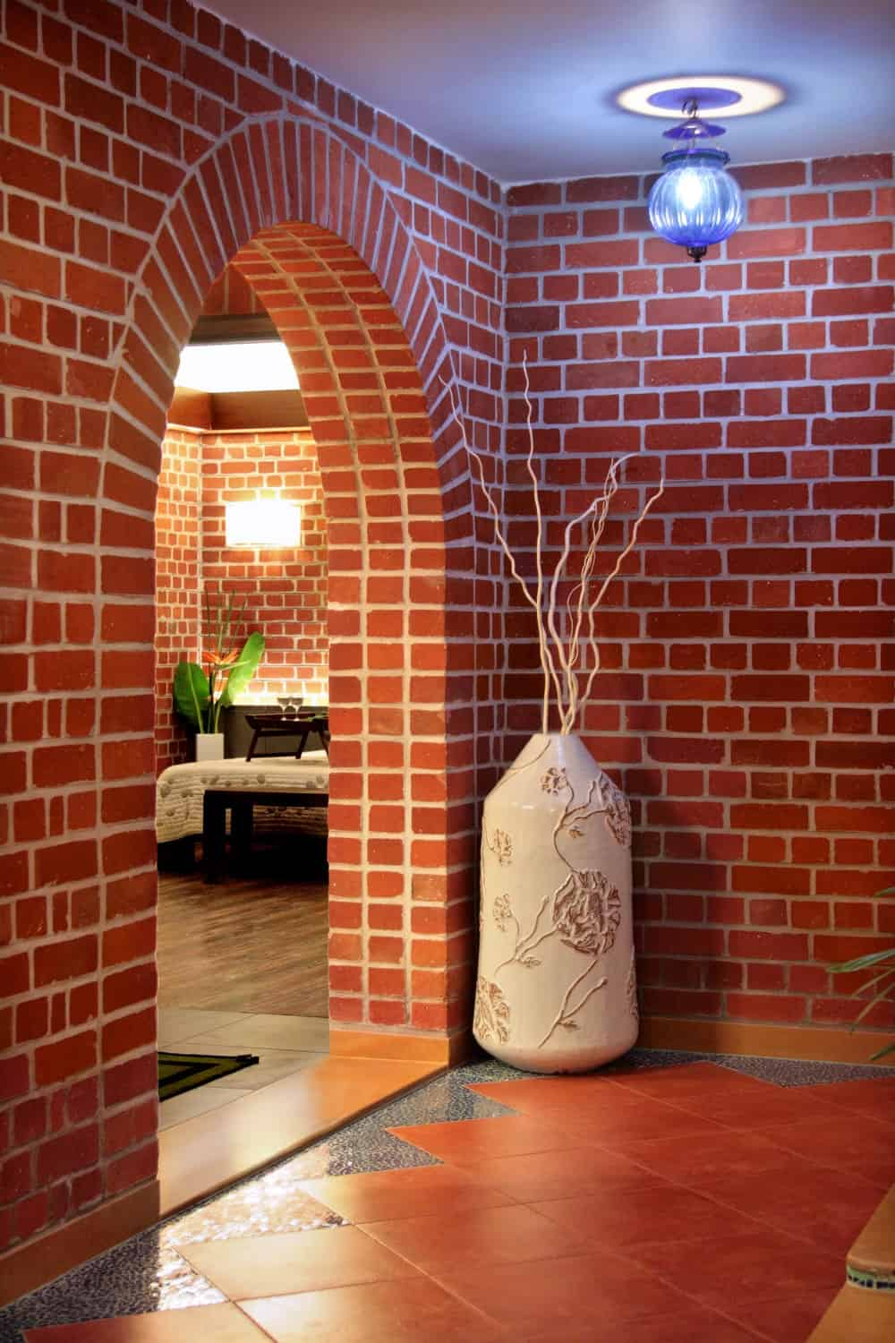 This is the brick arched entryway into the bedroom adorned with a large vase and a modern lighting.